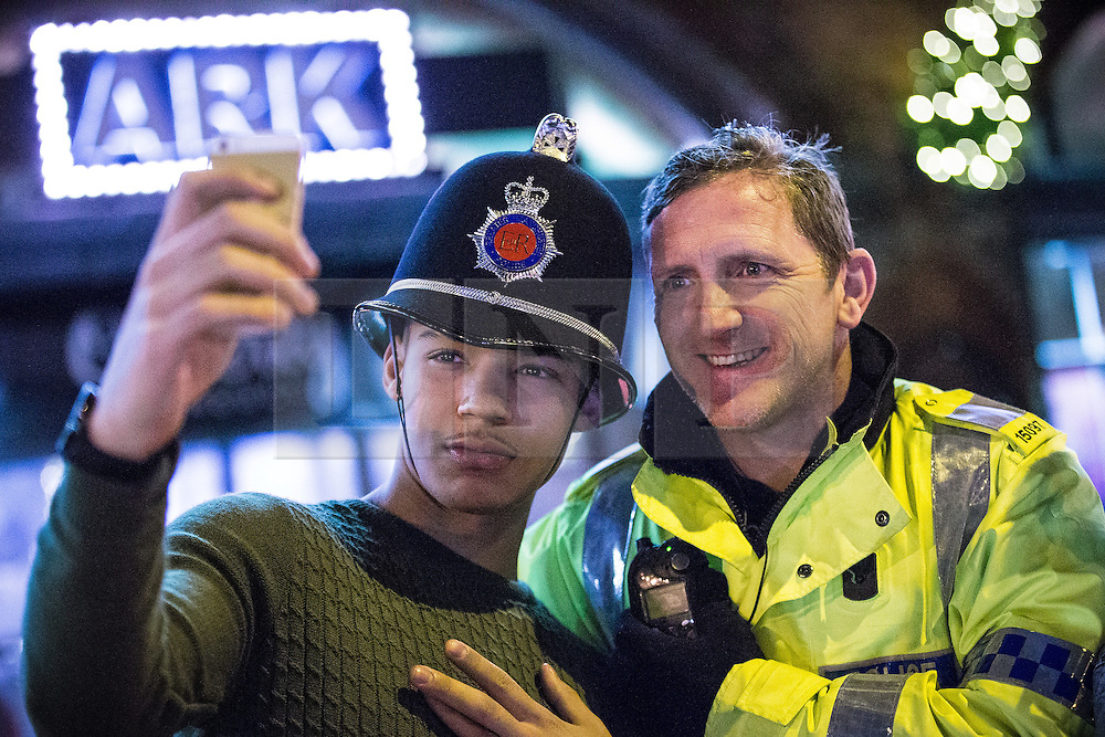 """© Licensed to London News Pictures . 19/12/2015 . Manchester , UK . A man poses for a selfie with a police constable whilst wearing his helmet . Revellers in Manchester enjoy """" Mad Friday """" - also known as """" Black Eye Friday """" - the day on which emergency services in Britain are typically at their busiest , as people head out for parties and drinks to celebrate Christmas . Photo credit : Joel Goodman/LNP"""