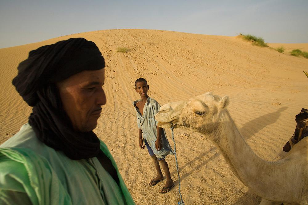 Tuareg man and boy with camel in the desert around Timbuktu, Mali.