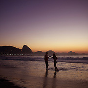 A couple enjoy a tender moment as they witness the amazing sunrise at Rio de Janeiro's most famous beach Copacabana with Sugar Loaf mountain in the distance. Rio de Janeiro, Brazil. 21st July 2010. Photo Tim Clayton.