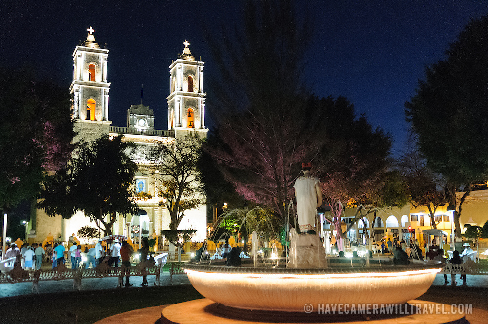 At left is the Cathedral of San Gervasio (Catedral De San Gervasio) and in the foreground is a foutain with a statue in the middle of Valladolid's main square. The square is a popular place to visit at night.