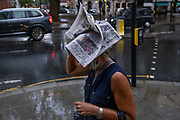 During an early evening downpour in Sloane Square, a woman covers her head with the latest edition of the Evening Standard newspaper, on 24th August 2020, in London, England.