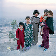 Young Afghan girls on hill top overlooking Nadir shah and Kabul. Names, right to left:  Historai, 11, Sheba , 2, Rifer, 10, Soloha, 9, Tina 4 ( all names spelt  phonetically).<br /> Children have been the primary victims of more than two decades of conflict. Of the estimated 1.5 million people killed during this period, some 300,000 were children. Abduction and trafficking in children is now a rapidly growing threat, with the most common forms of trafficking being child prostitution, forced labour, slavery, servitude and the removal of body organs.