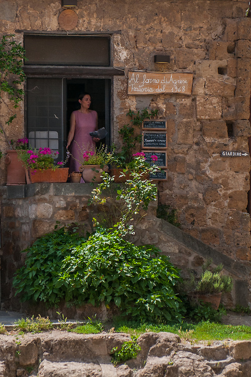 """A woman exits from a typical shop in the streets of the village of Civita di Bagnoregio.<br /> Civita di Bagnoregio is a town in the Province of Viterbo in central Italy, a suburb of the comune of Bagnoregio, 1 kilometre (0.6 mi) east from it. It is about 120 kilometres (75 mi) north of Rome. Civita was founded by Etruscans more than 2,500 years ago. Bagnoregio continues as a small but prosperous town, while Civita became known in Italian as La città che muore (""""The Dying Town""""). Civita has only recently been experiencing a tourist revival. The population today varies from about 7 people in winter to more than 100 in summer.The town was placed on the World Monuments Fund's 2006 Watch List of the 100 Most Endangered Sites, because of threats it faces from erosion and unregulated tourism."""