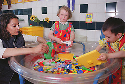 Nursery school children helping teacher to clean toys in large wash basin,