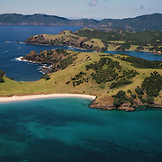 An panoramic aerial view of The Bay of Islands, North Island, New Zealand. The Bay of Islands boasts a unique coastline sheltering over 150 small islands in its arms. Once a seafaring and whaling region the Bay of Islands is today a popular tourist destination recognized for it's cultural heritage as well as it's amazing scenery and wildlife. Small towns are scattered along the coastline. Water-based activities, include kayaking, swimming with dolphins, game fishing and boating. Whales and dolphins can often be seen in the bay. Bay of Islands, New Zealand. Photo Tim Clayton