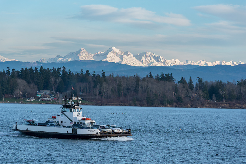 The Whatcom Chief ferry crossing Hale Passage in Washington.  The Sisters group of peaks in the Cascade Range rise in the background.