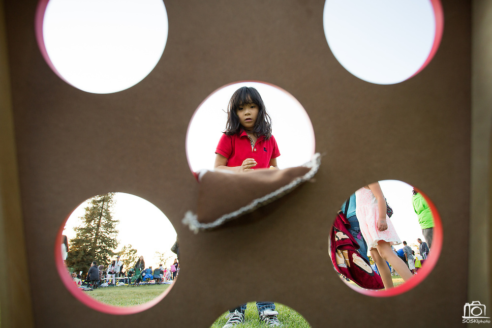 Eliana Coa-Biu, 7, tosses a bean bag during a game of Cornhole during the 6th Annual District 4 National Night Out Resource Fair and Movie Night at Northwood Park in San Jose, California, on August 6, 2013. (Stan Olszewski/SOSKIphoto)