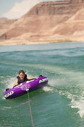 North America, Arizona, Page,  Lake Powell.  Boy (age 12) tubing behind motorboat.  MR