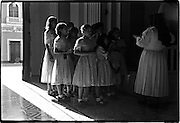 Group of young singers is led by a nun at the back of the church.