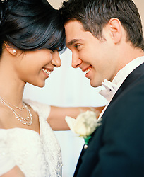 Close up of bride and groom standing face to face smiling