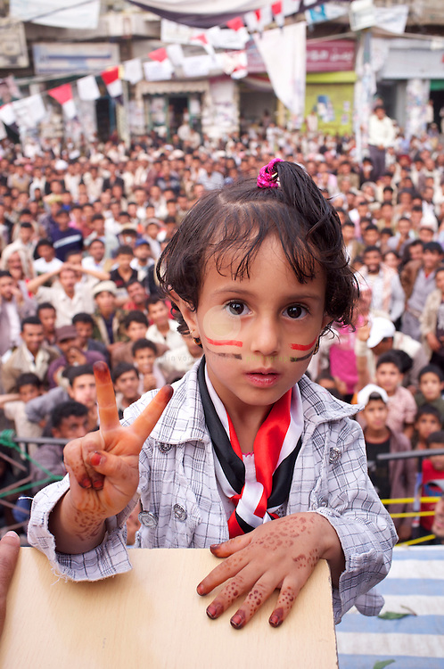 Turmoil in Yemen: ASIA, YEMEN, SANA, 20.06.2011: Anti-government protesters near Change Square in Sana, Yemen. A young girl shows the Victory sign, while protesters in the background wait for the next speaker to appear on stage.