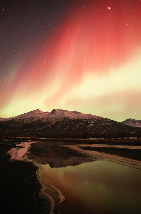 Alaska. Palmer. Aurora borealis or northern lights above Knik River and Chugach Mts.