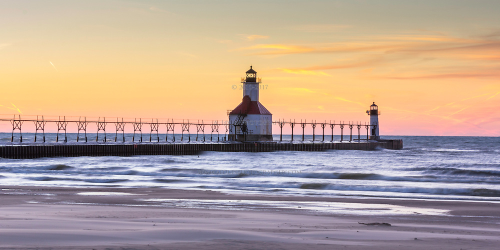 The setting sun leaves the sky aglow in warm colors over the lighthouse of St. Joseph, MI