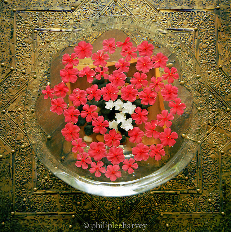 Flower petals float on water in a glass bowl. Kerala, India.