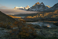 Early mornign fog lifting out of the valley with the dramatic mountain backdrop of Torres del Paine National Park, Chile