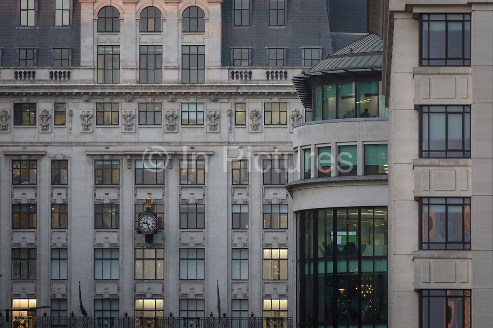 The clock face of the House of Fraser department store and a business meeting on the top floor of corporate offices in late afternoon in the heart of the Square Mile, the capitals historical and financial centre, on 1st November 2017, in the City of London, England.
