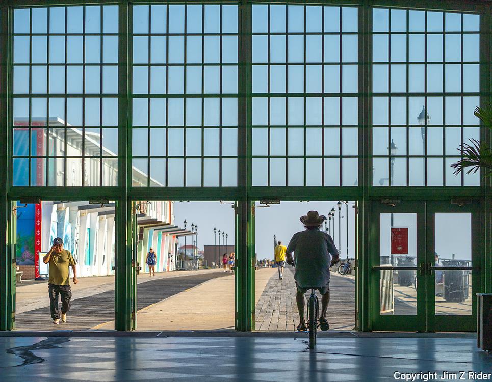 A man rides his bike through the Convention Center along the boardwalk