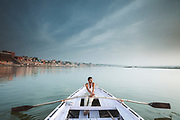 A ferryman rowing a boat on the river Ganges in the early morning, River Ganges, Varanasi, India