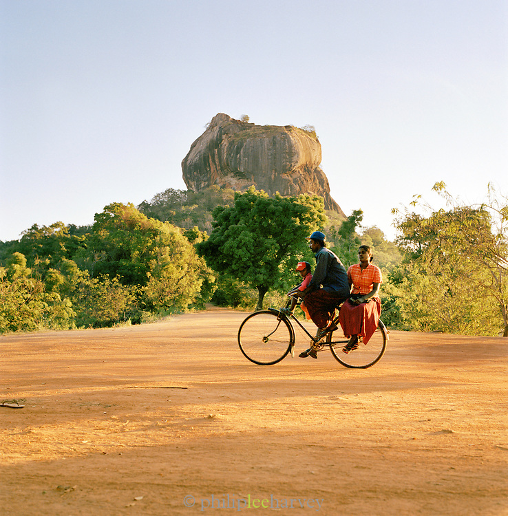 A young family cycles past in front of the rock fortress of Sigiriya, Sri Lanka, Asia