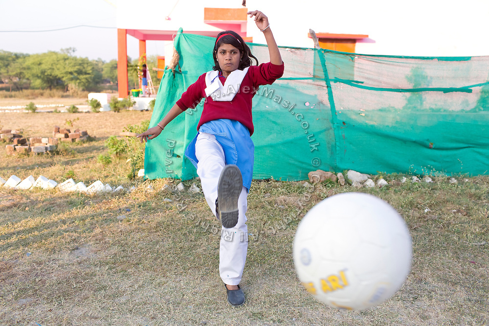 Ritu Gaur, 13, is kicking a soccer ball in front of the Jamoniya Tank Girls Hostel, near Sehore, Madhya Pradesh, India, where the Unicef India Sport For Development Project has started in 2012. Covering 313 state-run girls' hostels and 207 mixed hostels in Madhya Pradesh, the project ensures that children from Scheduled Tribes (ST) and others amongst the poorest people in India, can easily access education and be introduced to sports. Field workers from Unicef also oversee their nutrition and monitor the overall conditions of each pupil.