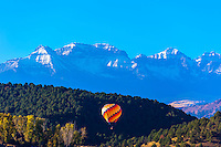 Hot air balloon flying with the Sneffels Range in background, Ridgway, Colorado USA.