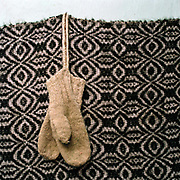 A pair of hand knitted woollen mittens hanging on a wall at a sheepfold in Lunca Ilvei, Romania