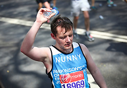 © Licensed to London News Pictures. 22/04/2018. London, UK. A man runner pours water on his head to cool off during the 2018 London Marathon which is being run in unusually warm temperatures for April. This years event is being started by HRH Queen Elizabeth II. Photo credit: Tom Nicholson/LNP