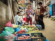 06 AUGUST 2015 - KATHMANDU, NEPAL:  People buy fruits and vegetables at a street stand in Kathmandu.     PHOTO BY JACK KURTZ