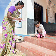 CAPTION: Steps prove a significant challenge for Ashwin, who has diplegia and can only get around unassisted if on his hands and knees. The Chamkol programme therefore provides for School Inclusion Audits and Plans with a view to correcting these flaws. LOCATION: Mangala Hosuru (village), Kasaba (hobli), Chamrajnagar (district), Karnataka (state), India. INDIVIDUAL(S) PHOTOGRAPHED: Nagamma (left) and Ashwin (right).