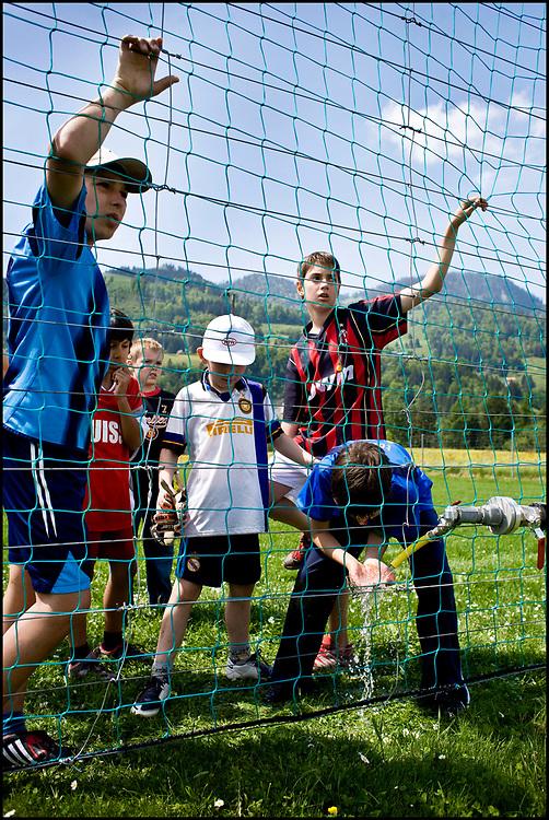 Zwitserland. Chamey, 23-05-2008.<br /> Kinderen in hun favoriete voetbalshirt spelen voetbal. Dorst hebben ze na een partijtje voetbal.<br /> Foto: Patrick Post