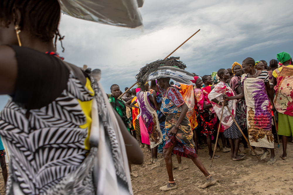 Community members carry a load of non-food items, such as blankets and tarpaulin, distributed by NGOS, following devestating flooding, in Pibor, Boma State, South Sudan, on 6 November 2019 // Photo credit: UNICEF South Sudan/de la Guardia