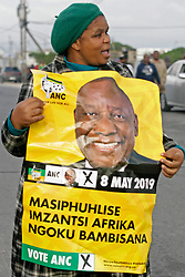Wednesday 8th May 2019.<br /> Monwabisi Park, Harare,<br /> Khayelitsha, Cape Town, <br /> Western Cape, <br /> South Africa.<br /> <br /> SOUTH AFRICAN GENERAL ELECTIONS 2019!<br /> <br /> SOUTH AFRICAN PROVINCIAL AND NATIONAL ELECTIONS 2019! <br /> <br /> An ANC supporter wears ANC colours as she walks past with an ANC elections poster outside the voting station at Monwabisi Park, Harare in Khayelitsha near Cape Town, Western Cape, South Africa.<br /> <br /> Registered South African Voters head to the various IEC (Independent Electoral Commission) Voting Stations where they are registered to vote as they cast their votes and take part in voting and other activities on Voting Day 8th May 2019 during the South African General Elections 2019. Voters from across the nation stood in queue's along with many others to vote in the Provincial and National Elections being held in South Africa on Wednesday 8th May 2019.   <br />  <br /> Copyright © Mark Wessels. All Rights Reserved. No Usage Without Permission.<br /> <br /> PICTURE: MARK WESSELS. 08/05/2019.<br /> +27 (0)61 547 2729.<br /> mark@sevenbang.com<br /> studioseven@mweb.co.za<br /> www.markwesselsphoto.com