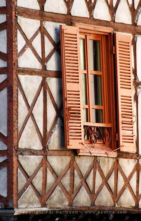 A building in the town with old half timber facade and wooden shutters.  Vienne, Isère Isere, France, Europe