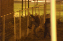 Youths in an urban area of Tyneside climbing a security fence for a building due for demolition; at night UK