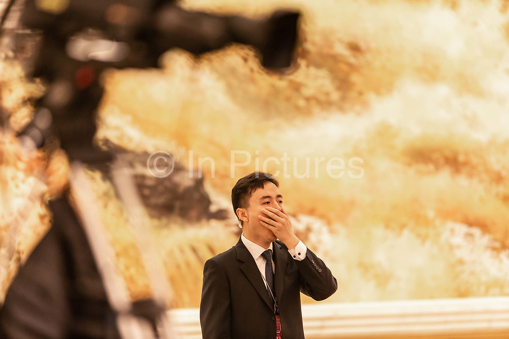 An attendant covers up as he yawns prior to Chinese premier Li Keqiangs press conference on the closing day of the 12th National Peoples Congress NPC at the Great Hall of the People in Beijing, China, on Wednesday, March 16, 2016.