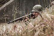 USA, Oregon, Astoria, Ft. Stevens State Park, living historian infantry soldier in fighting position behind cover. MR