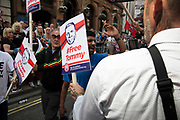 One vocally opposing protester is hauled away by police for his own safety while being baracked during a demonstration calling for the release from jail of former English Defence League, EDL, leader Tommy Robinson on June 9th 2018 in London, England, United Kingdom. Far right groups gathered shouting Free Tommy Robinson, blaming the police for his arrest and calling for free speech. Opposition groups gathered nearby.