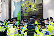 Metropolitan Police officers wait to arrest Extinction Rebellion activists who had taken part in a pink roadblock of Oxford Circus by women and FINT-identifying environmental activists during the third day of Impossible Rebellion protests on 25th August 2021 in London, United Kingdom. Extinction Rebellion are calling on the UK government to cease all new fossil fuel investment with immediate effect.