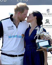 Meghan, Duchess of Sussex, wearing a navy blue dress by Carolina Herrera, and Prince Harry, Duke of Sussex kiss following the Sentebale ISPS Handa Polo at the Royal County of Berkshire Polo Club on July 26, 2018.