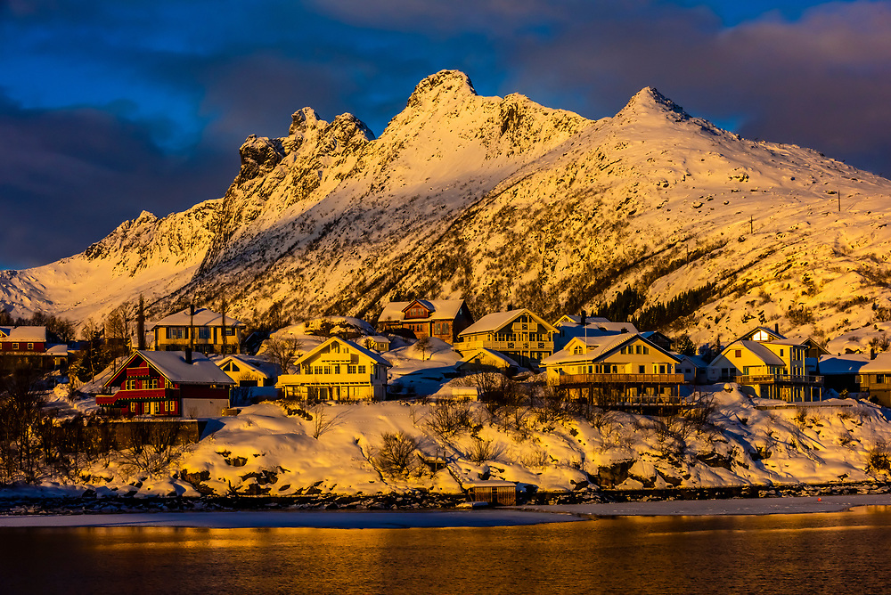 Houses surrounded by snow covered mountains, Svolvaer, on Austvagoya Island, Lofoten Islands, Arctic, Northern Norway.