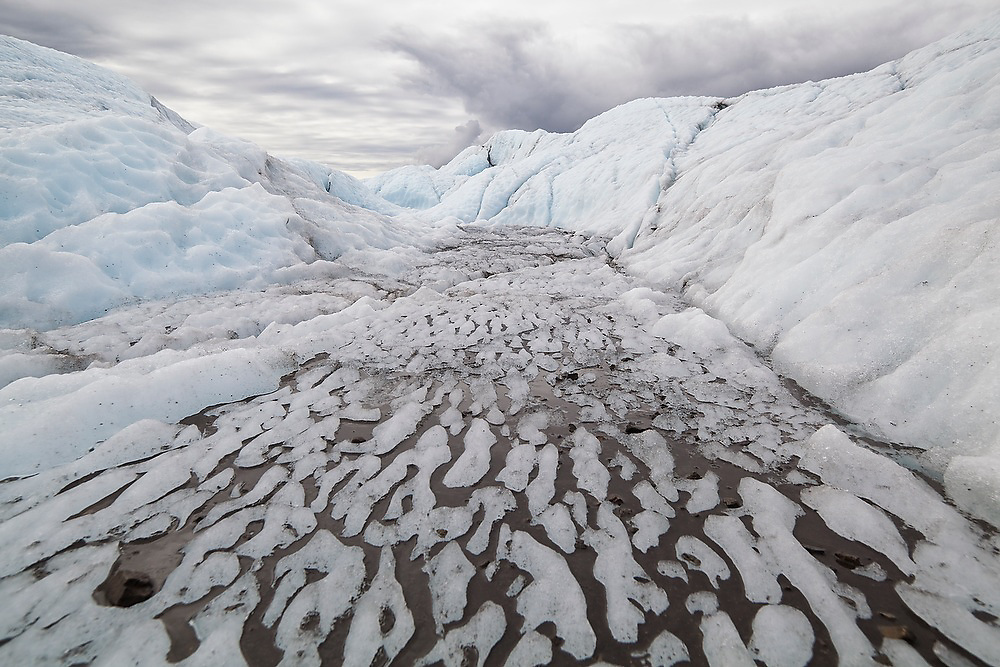 Sediment is deposited along meltwater channels, forming abstract black and white patterns in the ice on the dynamic surface of the Root Glacier, Wrangell-St. Elias National Park, Alaska