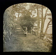 Magic lantern slide of woman standing in countryside next to a flight of steps through woodland, possibly the Lake District, England, UK c 1900