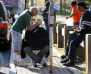 Cymerys moves his alfresco shop next to his vehicle in order to power up his clippers after the portable car battery he was using died.  Client Aaron Peck of Hartford receives a haircut from Cymerys  at the new location between parking meters, in Hartford, Conn.