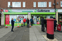 © Licensed to London News Pictures. 15/01/2021. LONDON, UK.  People line up outside Cullimore Chemist in Edgware, north west London, to receive their coronavirus vaccination.  Cullimore Chemist is one of 6 community pharmacy pilot sites across the country offering coronavirus vaccinations, with 200 more to come online in the next two weeks.  Three special purpose consulting rooms have been constructed, staffed by qualified vaccinators to administer the Oxford-AstraZeneca vaccine.  Proprietor Hassan Khan expects to be able to offer 1,200 jabs per week, but the current problem is a bottleneck in vaccine supply.  Photo credit: Stephen Chung/LNP