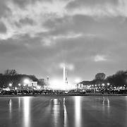 Lights from the masses of media outlets congregated on the National Mall on the eve of Inauguration is reflected on the frozen pool in front of the US Capitol building.