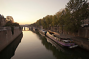 River barges moored on the banks of the River Seine beside the Notre Dame de Paris Cathedral in Paris, France