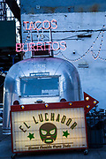 A retro silver airstream caravan converted into a Mexican street food cafe on South Side Street, Lower Manhattan, New York City, New York, United States of America. The neon sign above the caravan says Taco vs Burritos.