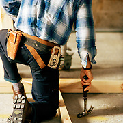 backside of male construction worker holding a hammer