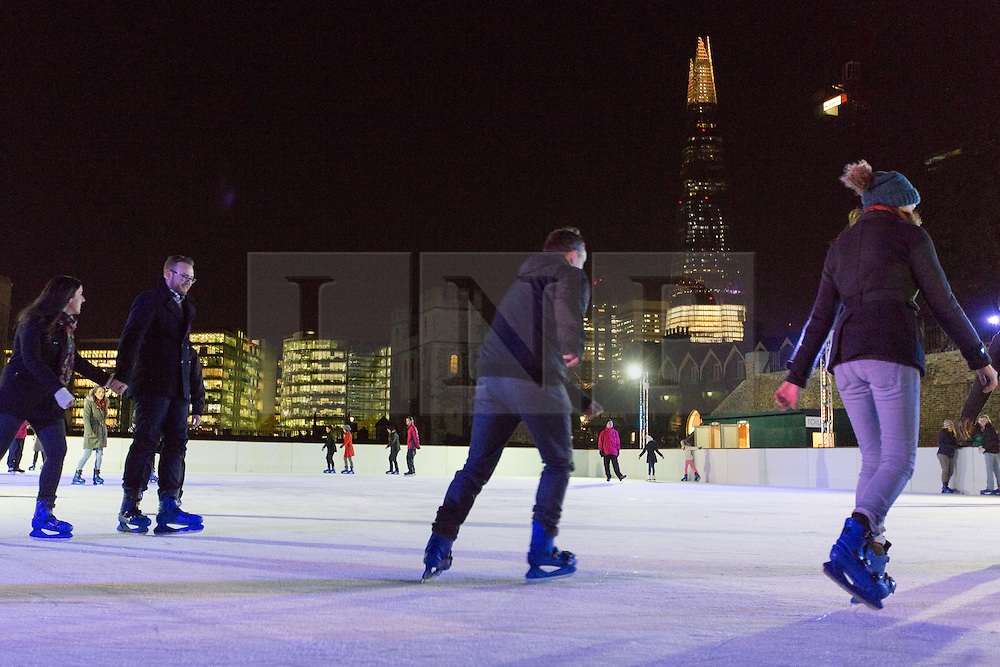 © Licensed to London News Pictures. 14/11/2013. London, UK. People ice skate at night on the Tower of London ice rink with a backdrop of the London Shard on 14 November 2013 at press night. The Tower of London ice rink opens on 16 November 2013. Photo credit : Vickie Flores/LNP