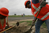 Construction workers Carlos Rodriguez (right) and Gustavo Espinoza (left) work on a drainage conduit outside of San Benito as Jay Johnson Castro passes by on his walk from Laredo to Brownsville